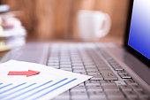 Laptop, bar chart, files, coffee mug on office desk