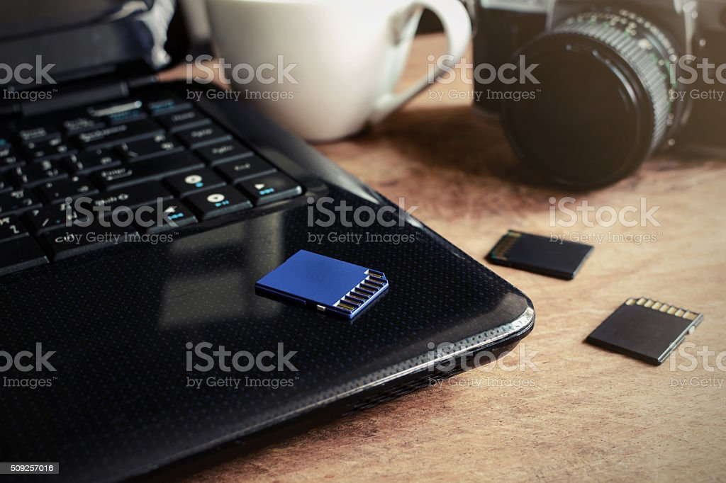 laptop, camera and a cup of coffee on wooden desk stock photo