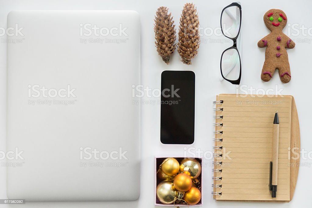 Laptop closed, mobile phone, office supply and Christmas decoration stock photo