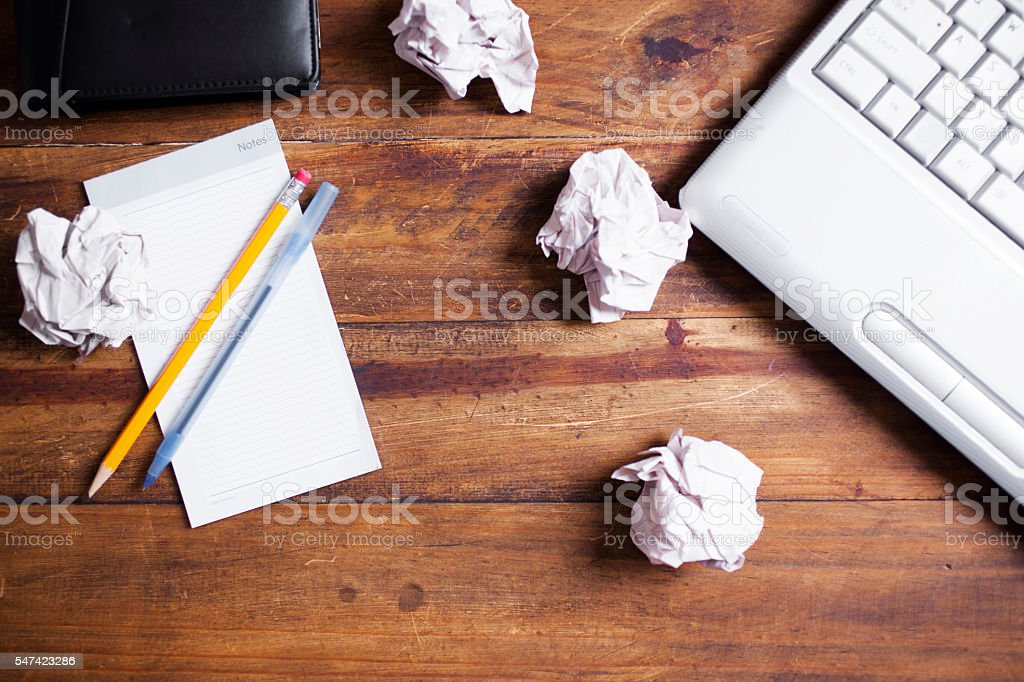 Laptop computer, crumpled paper balls, notepad on desk. stock photo