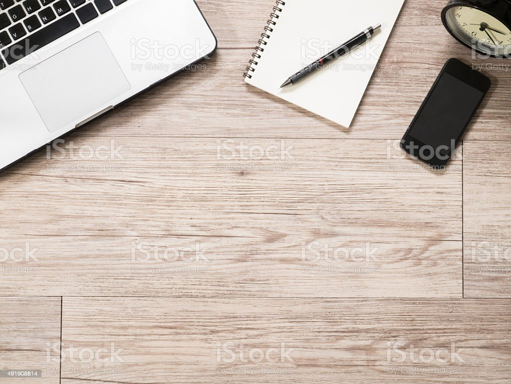 Laptop computer, notebook , smartphone and alarm clock on wooden desk stock photo
