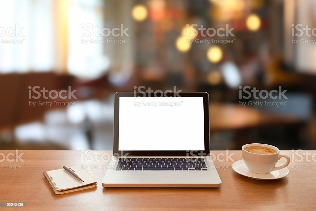 Laptop computer on cafe table with defocused background stock photo