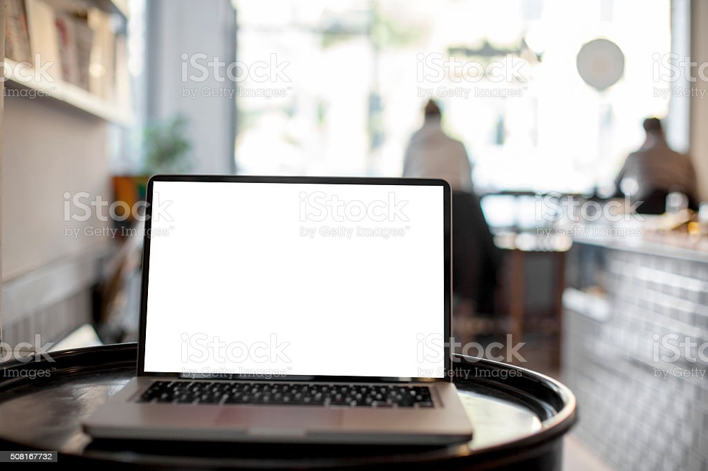 Laptop computer on cafe table with defocused stock photo