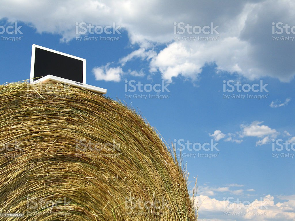 Laptop Computer on Large Round Hay-Bale Under Dramatic Blue Sky royalty-free stock photo