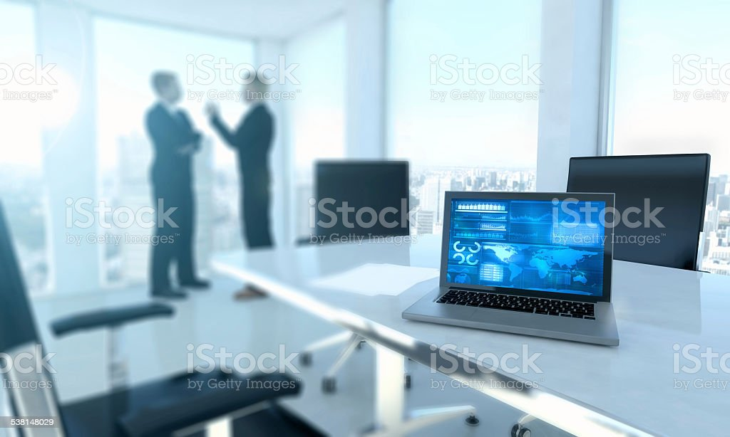 Laptop computer on office desk with business men stock photo