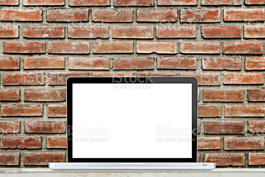 Laptop computer on table with brick wall background. stock photo