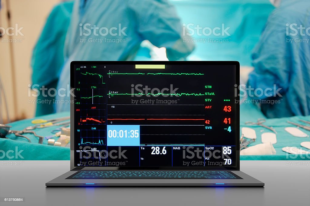laptop computer on table,operating room seen in the background stock photo