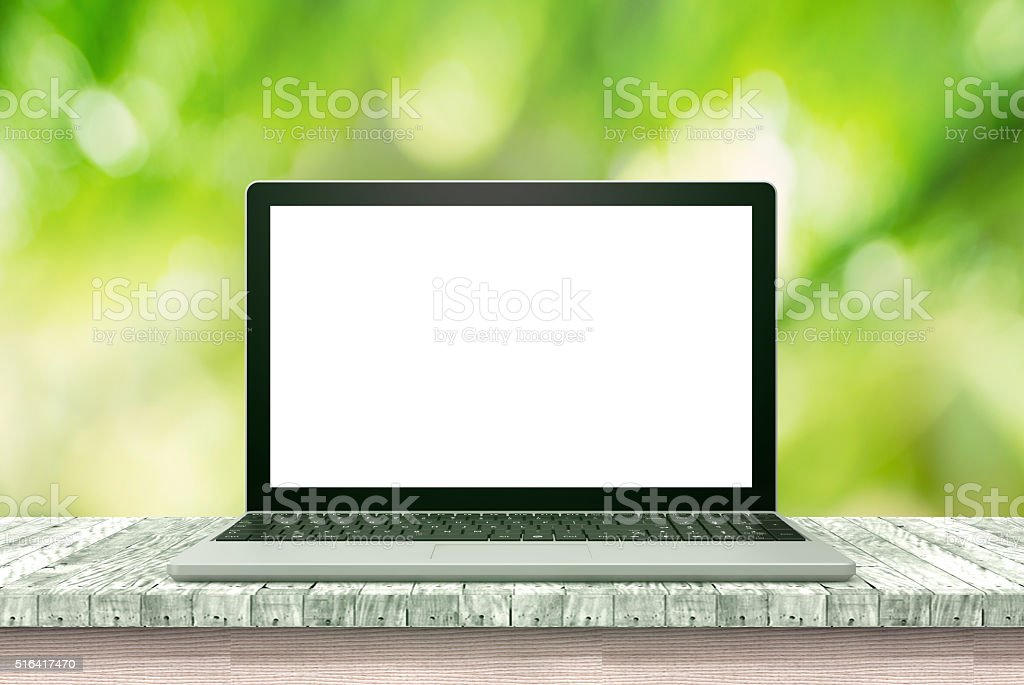 laptop computer on wood table green background stock photo