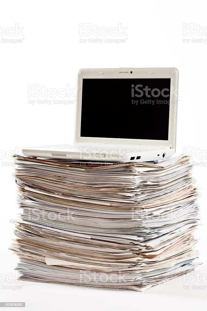 laptop computer over pile of documents royalty-free stock photo