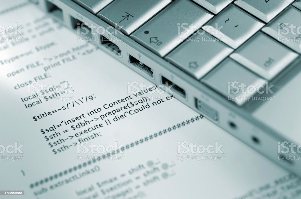Laptop computer sits atop a printout of a computer program. royalty-free stock photo