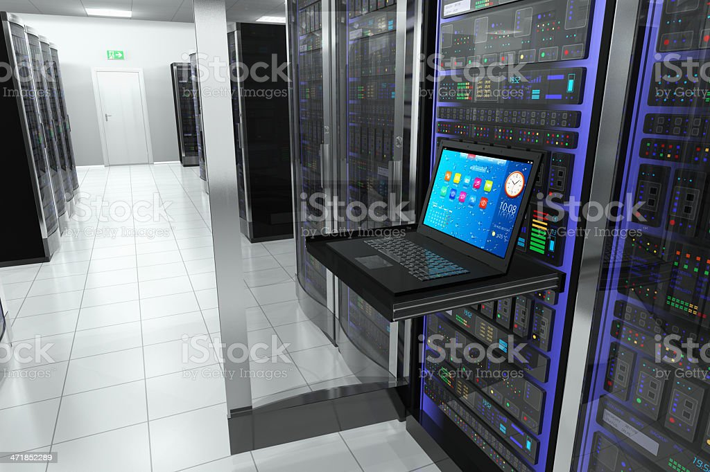 A laptop computer with a lit screen rests on a shelf in a computer...