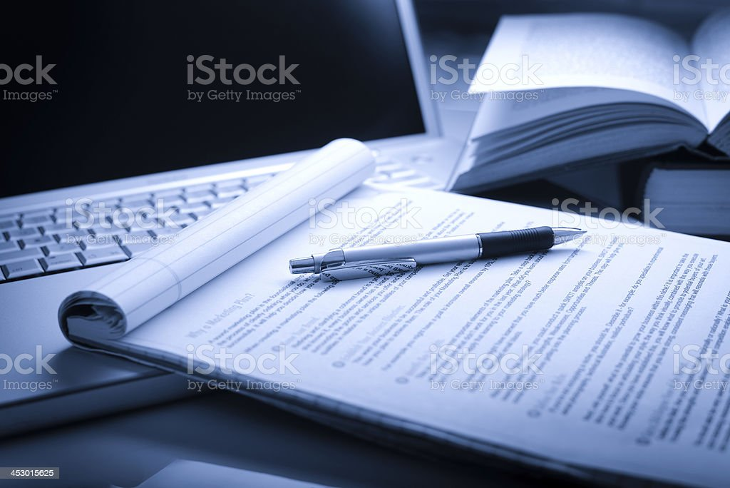 Laptop computer with books, pen and legal pad stock photo