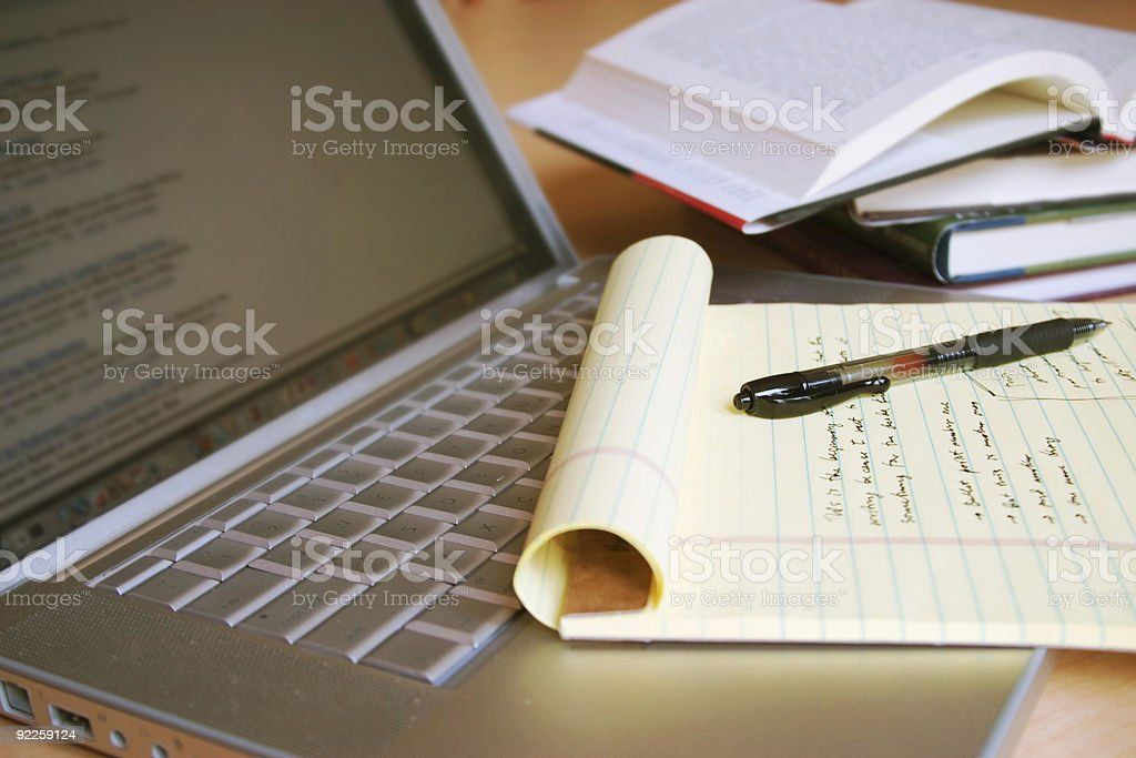 Laptop computer with books, pen and yellow legal pad stock photo