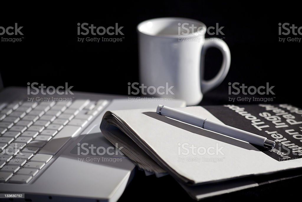 Laptop computer with newspaper, pen and white mug royalty-free stock photo