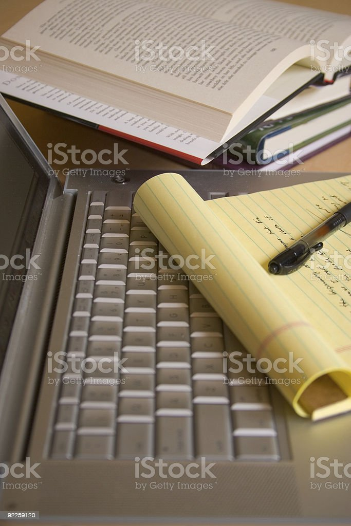Laptop computer with yellow pad, pen, and books - Vertical stock photo