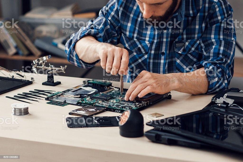 Laptop disassembling with screwdriver at repair stock photo