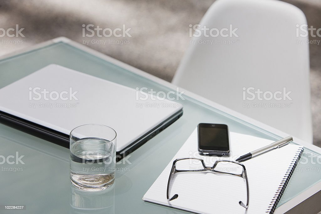 Laptop, eyeglasses, cell phone and notepad on table royalty-free stock photo