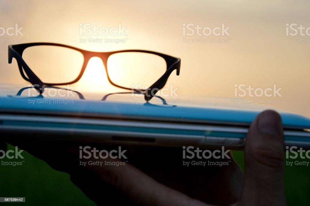 Laptop & glasses during sunset stock photo