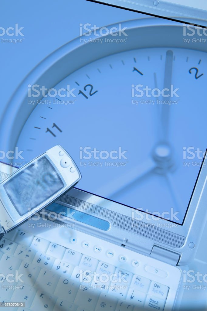 Laptop keyboard and clock synthesis stock photo