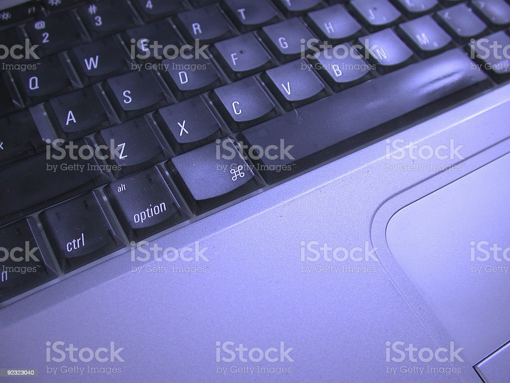 Laptop keyboard and trackpad with a blue hue royalty-free stock photo