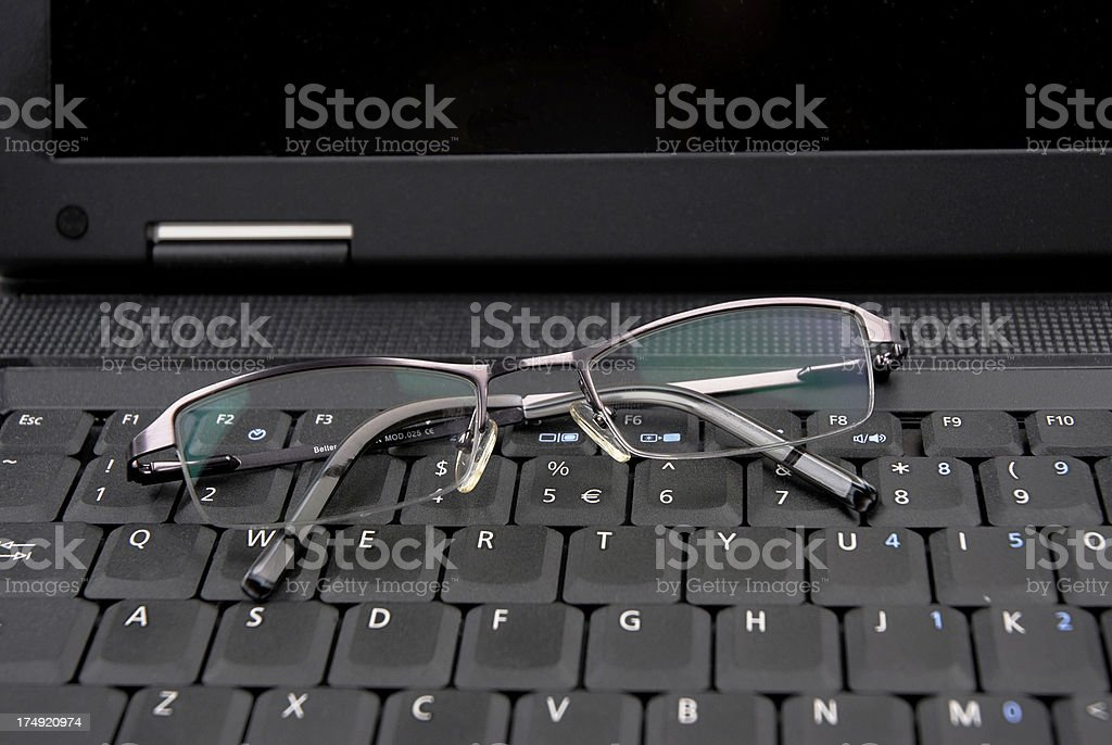Laptop keyboard with glasses royalty-free stock photo