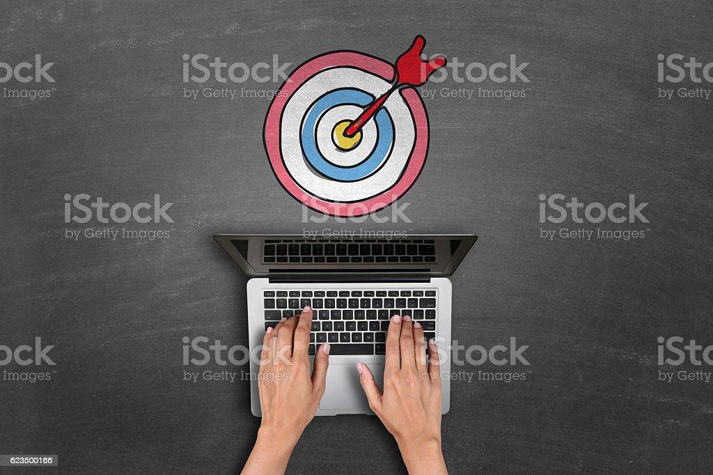laptop keypad in front of dartboard stock photo