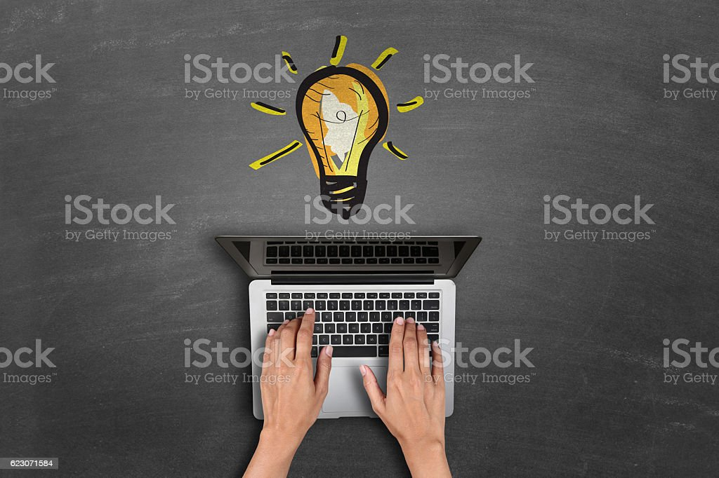 laptop keypad in front of light bulbs glowing stock photo