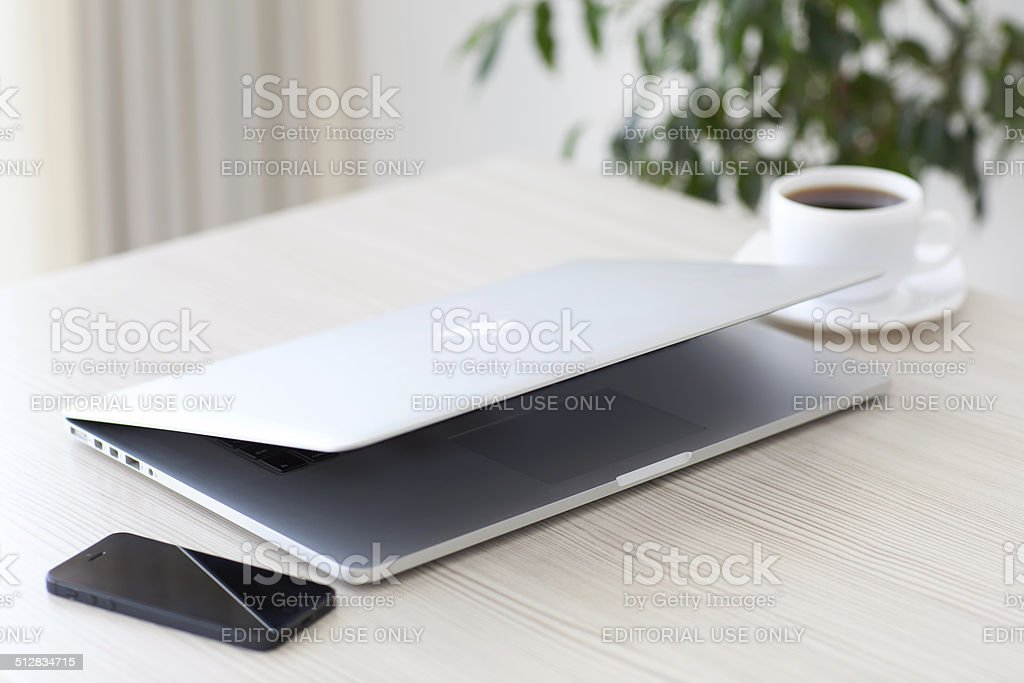 laptop MacBook Pro Retina and iPhone is lying on table stock photo