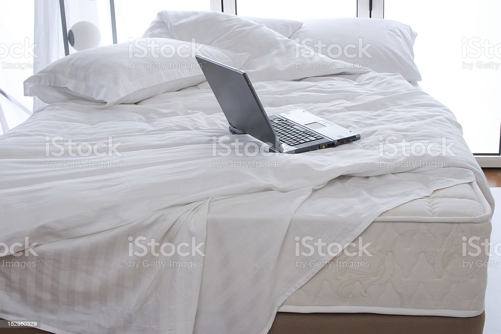 Laptop on a bed royalty-free stock photo