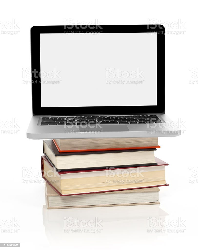Laptop on a stack of books stock photo