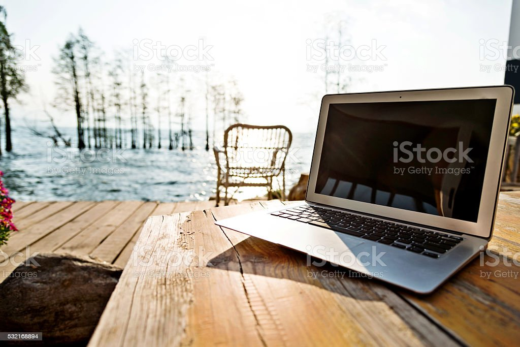 Laptop on table and lakeside stock photo