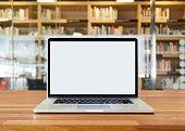 Laptop on table, on bookshelf background,blank screen