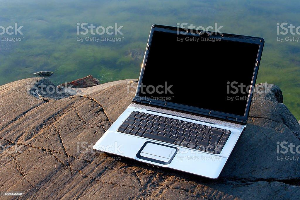 Laptop on the beach rock royalty-free stock photo