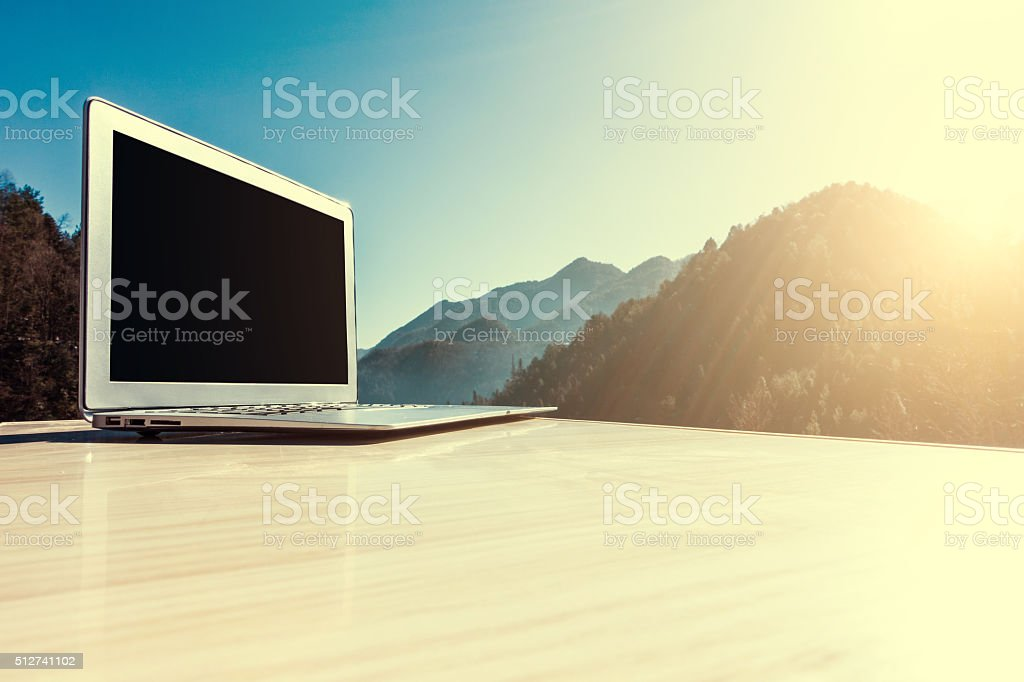 Laptop on wooden table with mountain background stock photo
