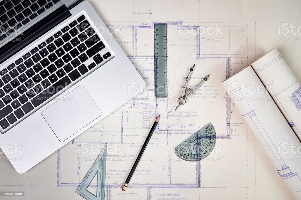 A laptop open with blueprints and architectural tools stock photo