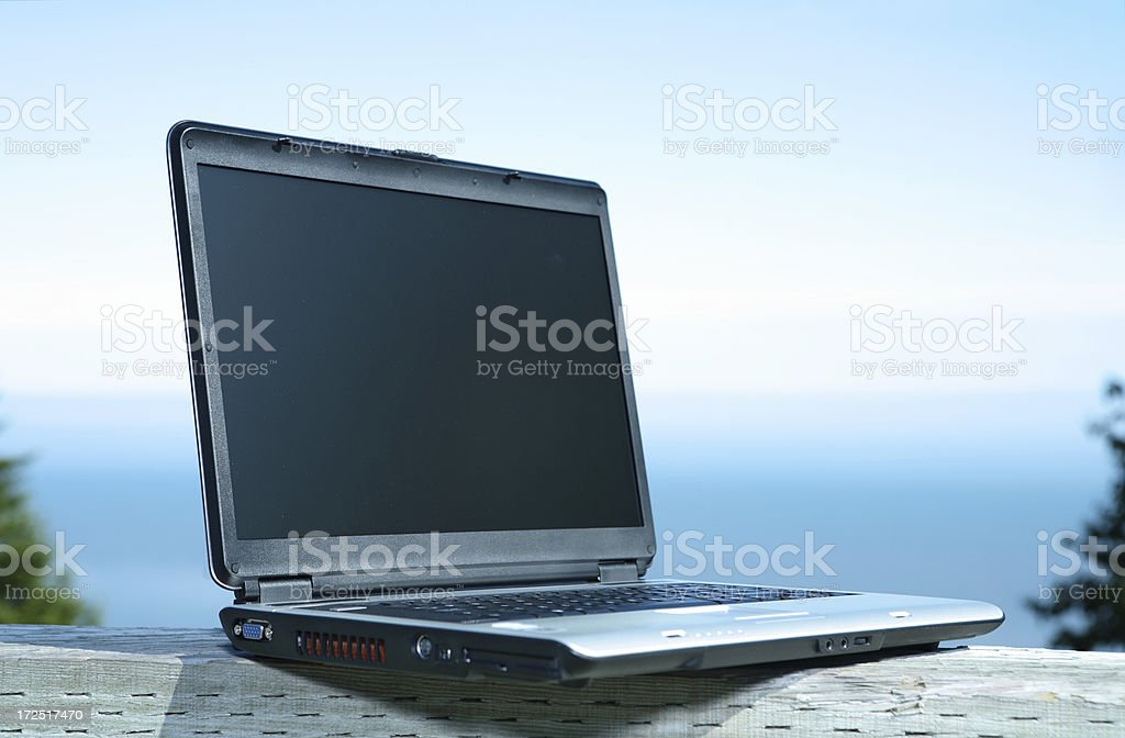 Laptop outdoors on wooden beam royalty-free stock photo