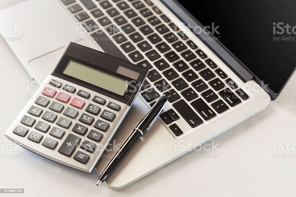 Laptop, pen and calculator stock photo