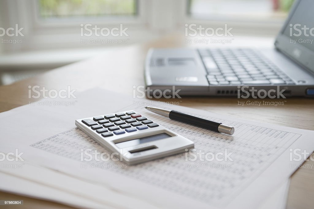 Laptop, pen, calculator & paperwork on table royalty-free stock photo