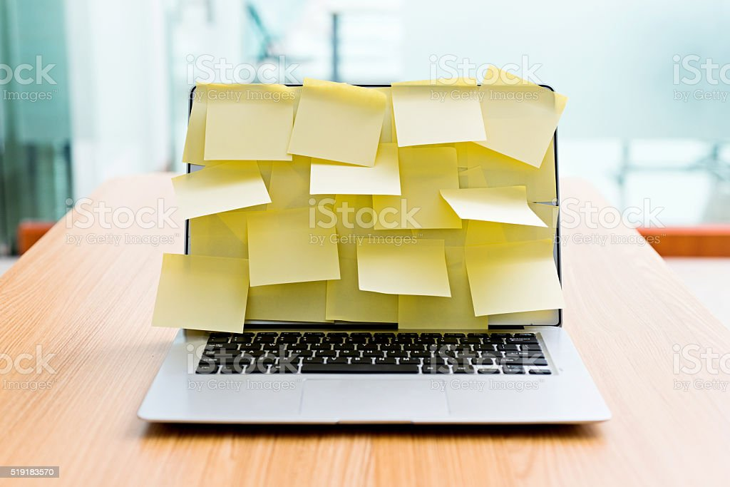 Laptop screen covered by adhesive notes stock photo