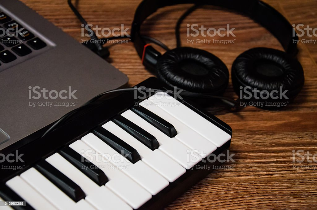 laptop, synthesizer and headphones on a wooden table stock photo