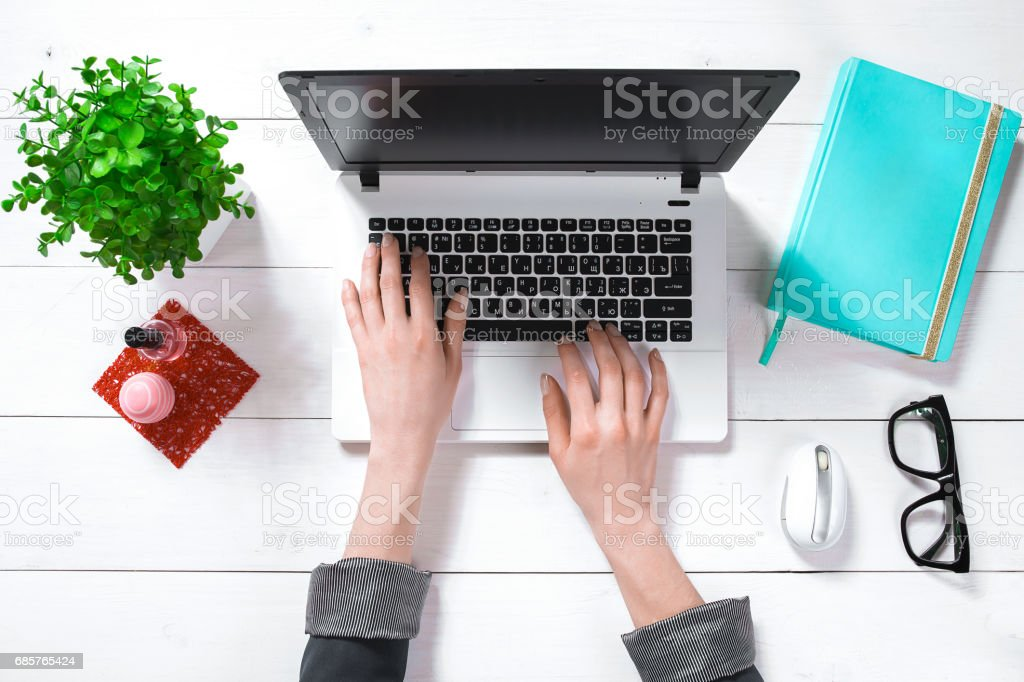 Laptop with blank screen and girl's hands. Flat lay, top view workspace stock photo