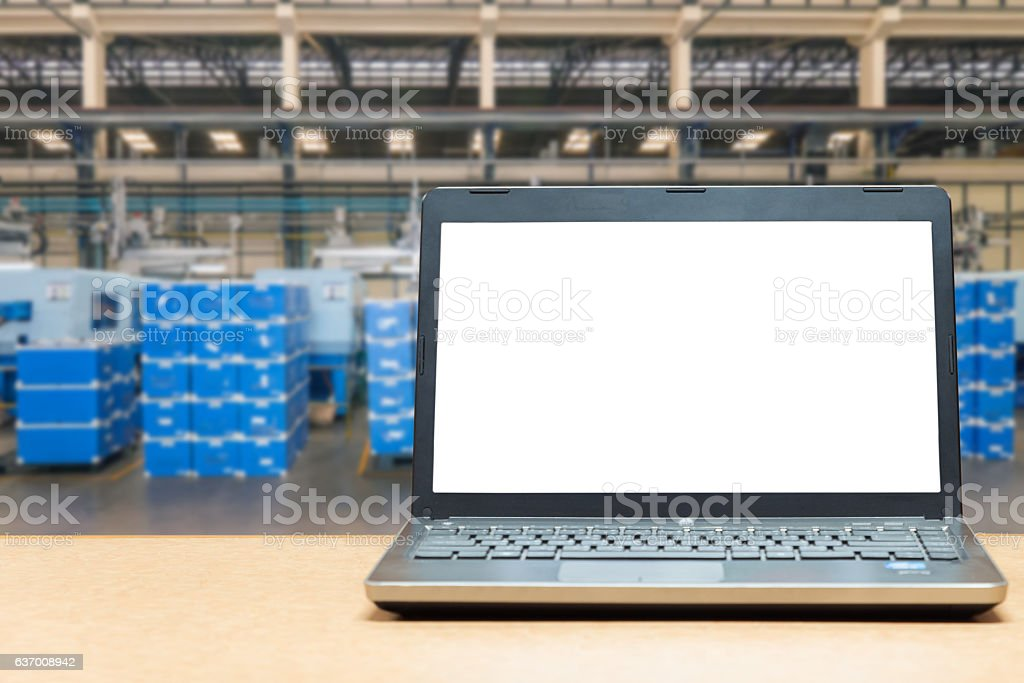 Laptop with blank screen on table with blur warehouse cargo stock photo