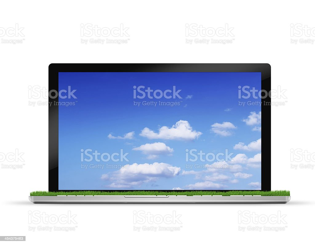 laptop with blue sky and green grass stock photo