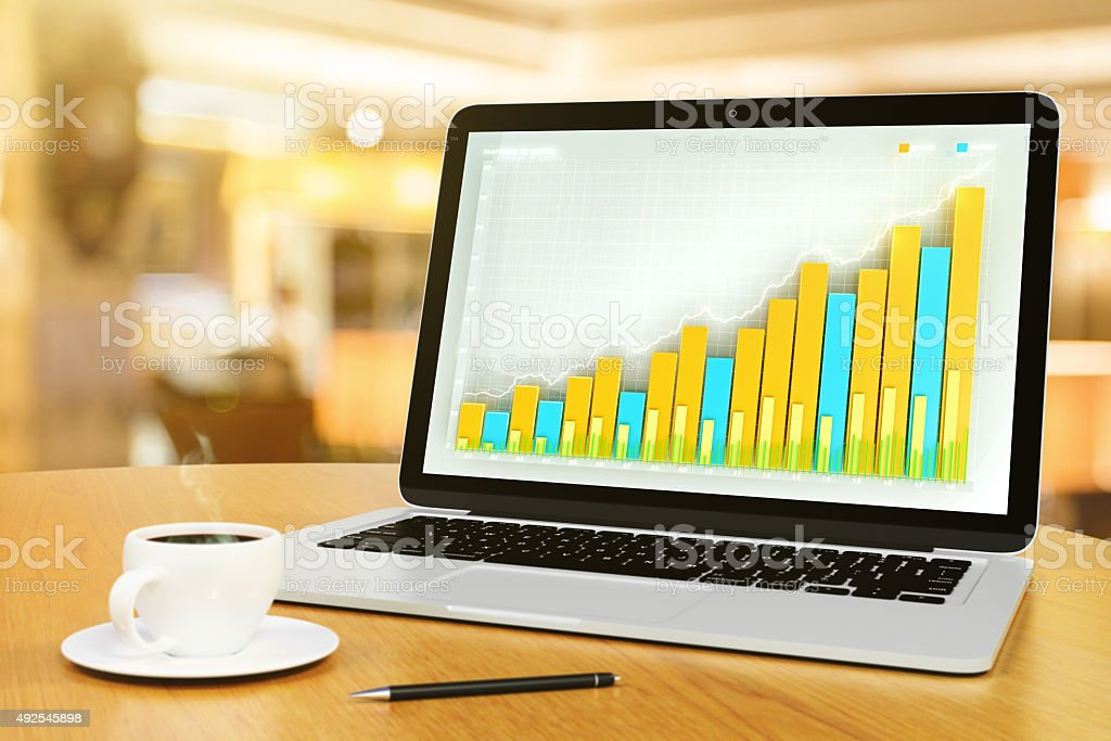 Laptop with business chart, pen and cup of coffee stock photo