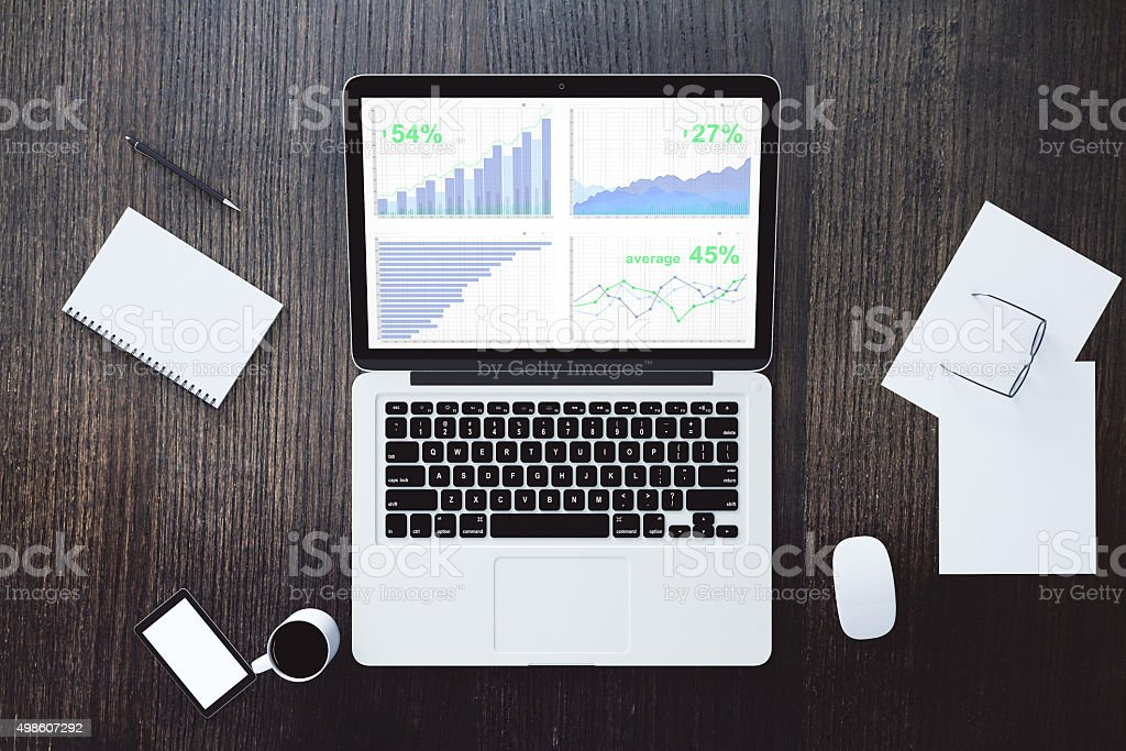 Laptop with business graph on the wooden desk stock photo