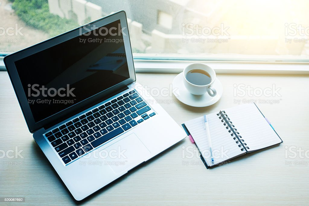 Laptop with coffee and notebook on desk stock photo