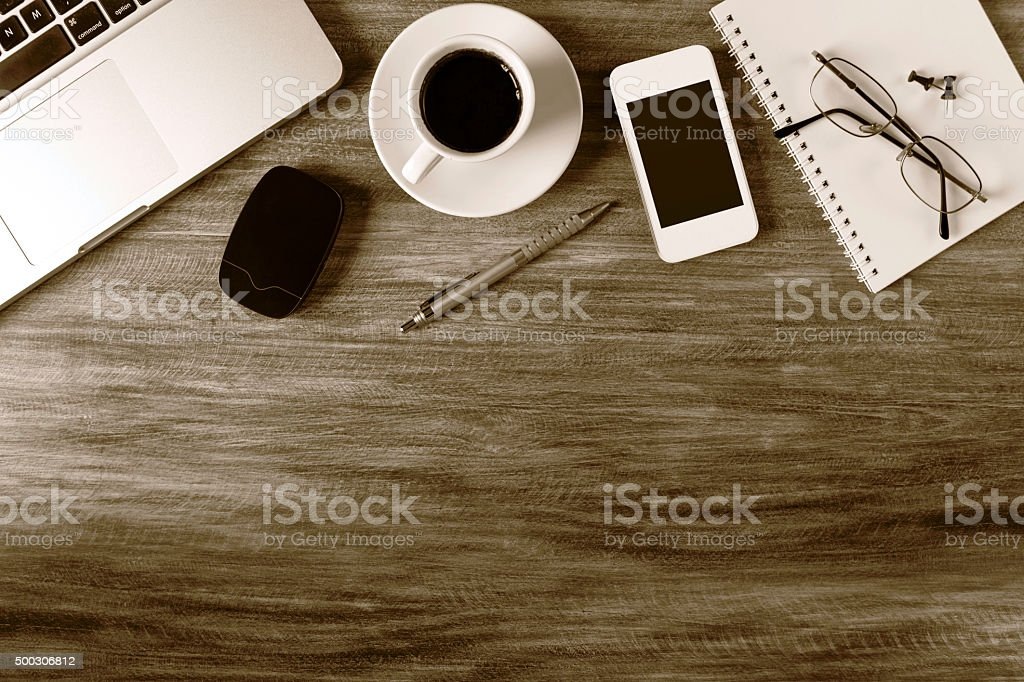 Laptop with coffee and office supplies on wooden desk stock photo