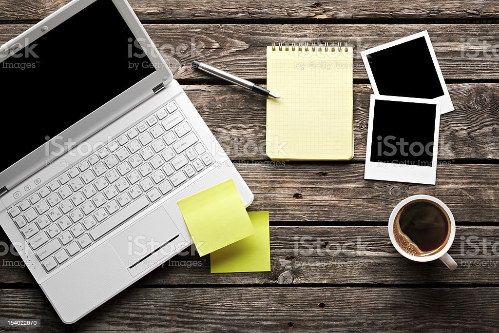 Laptop with coffee cup on old wooden table. stock photo