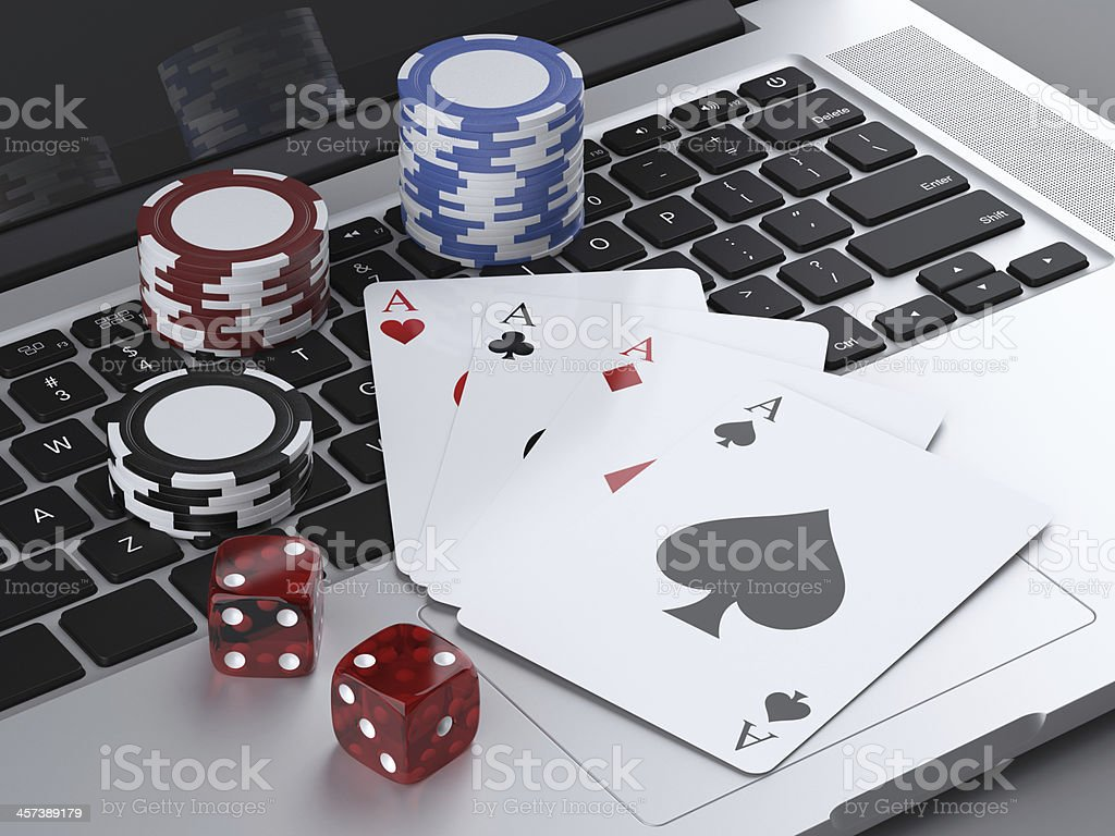 laptop with gambling chips and poker cards stock photo