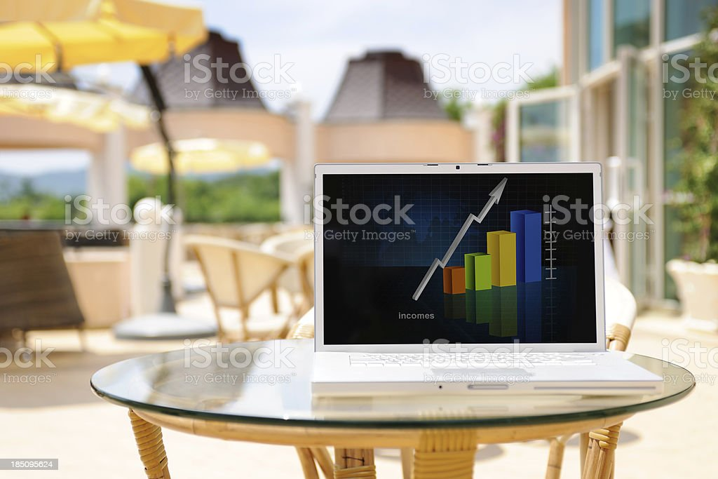 Laptop with graph on the screen at coffee shop patio royalty-free stock photo